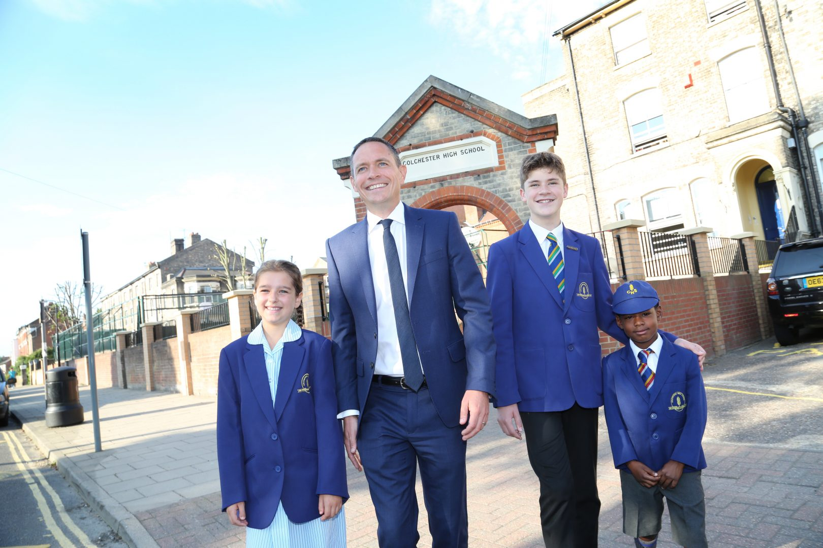 Headmaster walks with pupils across the school courtyard
